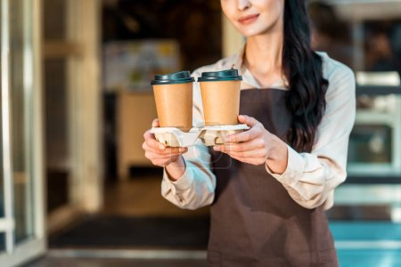 cropped image of waitress in apron holding two coffee in paper cups near cafe