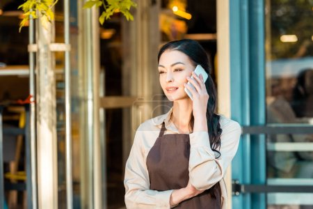 beautiful waitress in apron talking by smartphone and looking away near cafe