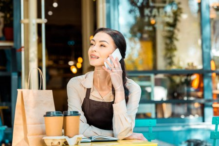Photo for Beautiful waitress in apron sitting at table and talking by smartphone on street near cafe - Royalty Free Image