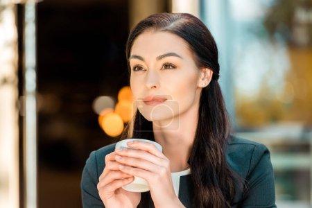 Photo pour Portrait de la belle femme tenant la tasse de café et en regardant loin de café de rue - image libre de droit
