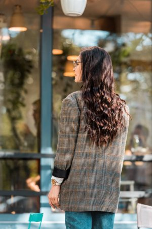 back view of beautiful woman in autumn outfit standing on street near cafe