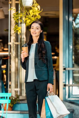Photo for Smiling attractive woman standing with shopping bags and coffee in paper cup on street near cafe - Royalty Free Image