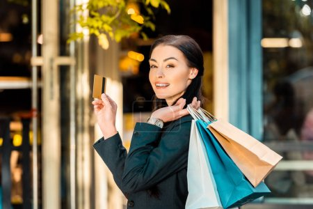 smiling beautiful woman holding credit card and shopping bags on street near store