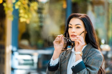 beautiful woman in autumnal jacket wearing glasses on street