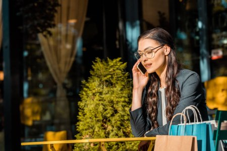 beautiful woman talking by smartphone at table at street cafe, shopping bags on chair