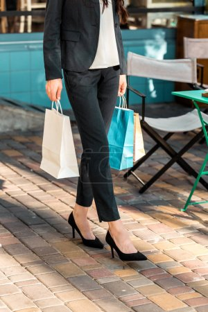 cropped image of woman walking with paper bags after shopping on street