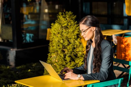 brunette focused businesswoman working with laptop on restaurant terrace