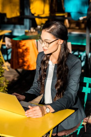 attractive young businesswoman working with laptop on restaurant terrace