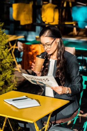 attractive woman holding coffee to go and reading business newspaper while sitting on cafe terrace