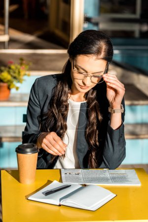 concentrated woman reading newspaper with coffee to go and planner on cafe terrace