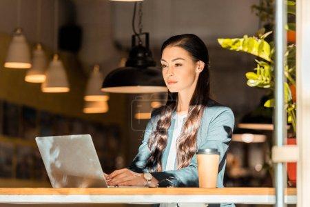 Photo pour Attrayant brunette pigiste travaillant avec ordinateur portable au café - image libre de droit