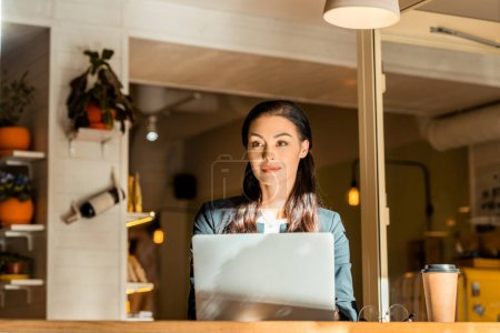 Photo for Beautiful female freelancer working with laptop at cafe with coffee cup - Royalty Free Image