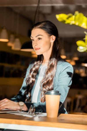 brunette freelancer working with laptop at cafe with coffee to go