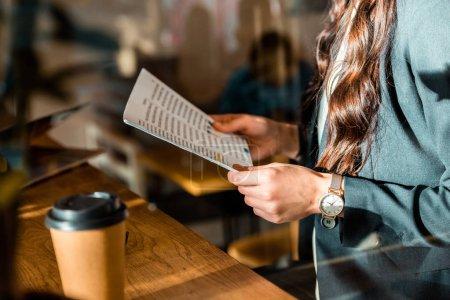 Photo pour Vue recadrée de femme d'affaires lecture du document au café avec café pour aller - image libre de droit