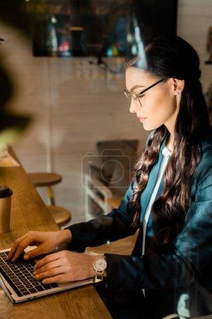 beautiful brunette teleworker in eyeglasses using laptop at restaurant