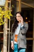 """Постер, картина, фотообои """"привлекательная женщина в модный пиджак, говорить на смартфоне у входа в ресторан"""""""