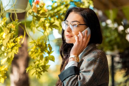 beautiful stylish woman in eyeglasses talking on smartphone