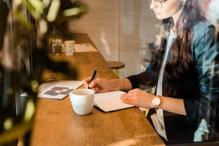 female freelancer writing in diary at table with coffee cup and business newspaper in coffee shop