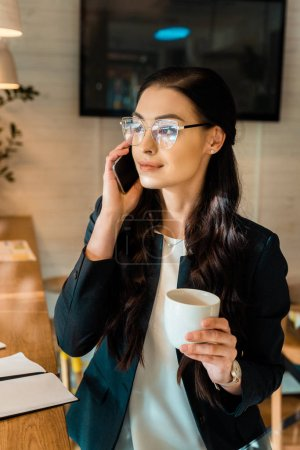attractive brunette businesswoman in eyeglasses talking on smartphone and holding coffee cup in coffee shop