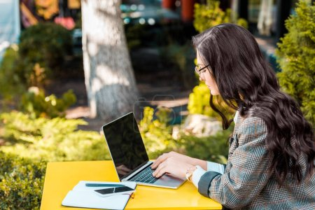 brunette female freelancer working with laptop at restaurant terrace