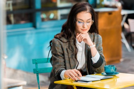 beautiful freelancer working on restaurant terrace with planner, smartphone and cup of coffee