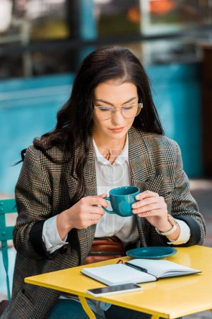 attractive freelancer holding coffee cup on restaurant terrace with planner and smartphone