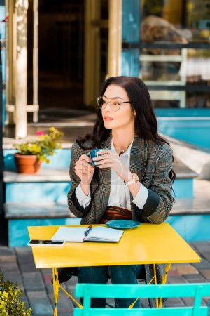 beautiful freelancer holding coffee cup on cafe terrace with planner and smartphone
