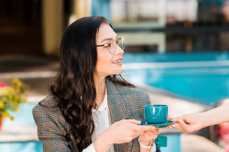 attractive woman taking coffee cup from waitress on restaurant terrace