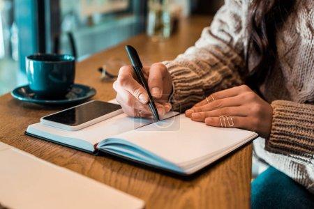 Photo pour Vue recadrée de l'écriture pigiste dans le planificateur avec smartphone dans le café - image libre de droit