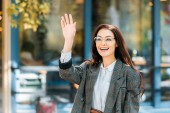 smiling woman in stylish jacket waving to someone on street