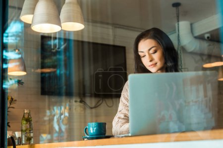 beautiful female freelancer with coffee cup working on laptop in cafe