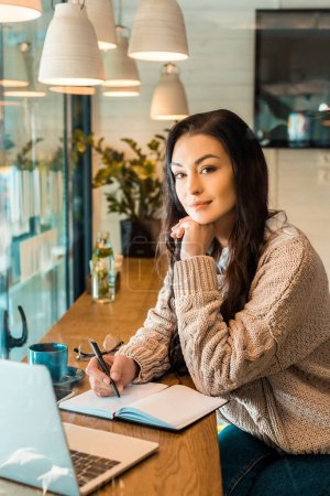 beautiful female freelancer working with planner and laptop in cafe