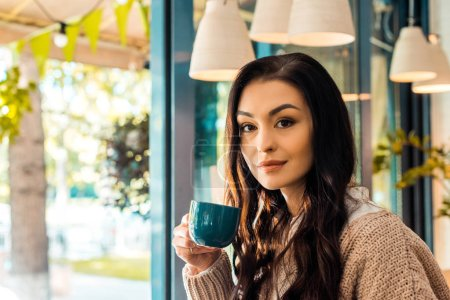 Photo for Beautiful woman in autumn sweater holding cup of coffee in cafe - Royalty Free Image