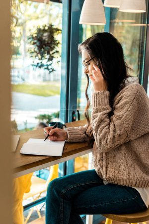 brunette female freelancer talking on smartphone and writing in diary in cafe