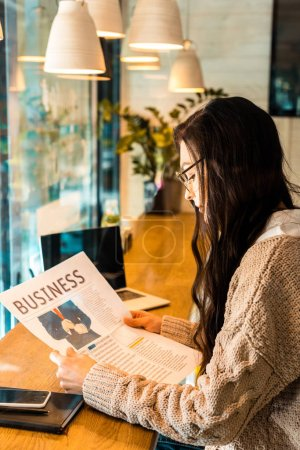 brunette woman reading business newspaper at cafe with laptop