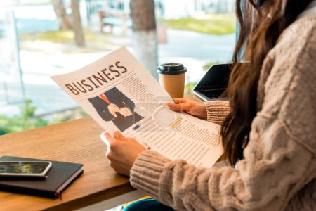 cropped view of woman reading business newspaper at cafe