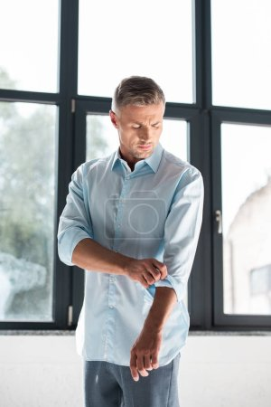 handsome adult man rolling up sleeves of shirt