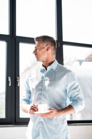 thoughtful adult man with cup of coffee looking at window