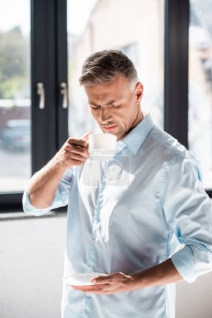 serious adult man drinking coffee in front of window