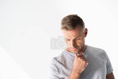 thoughtful adult man in blank grey t-shirt touching his chin and looking down isolated on white