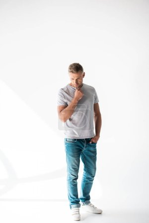 handsome adult man in blank grey t-shirt standing on white