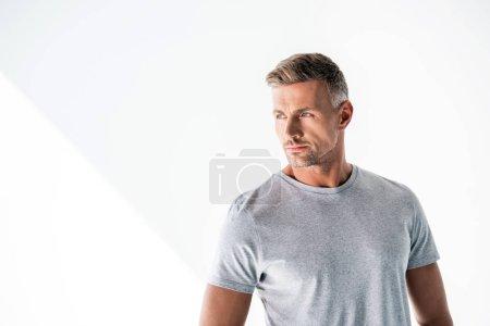 Photo pour Bel homme adulte en t-shirt blanc gris regardant loin isolé sur blanc - image libre de droit