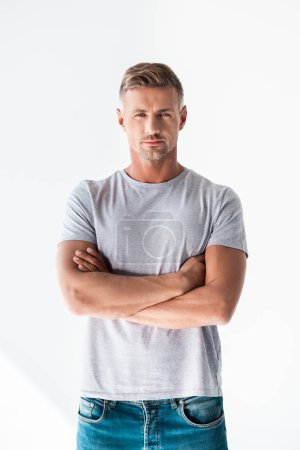 Photo for Handsome adult man in blank grey t-shirt looking at camera with crossed arms isolated on white - Royalty Free Image