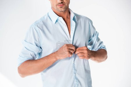 cropped shot of handsome adult man buttoning shirt isolated on white