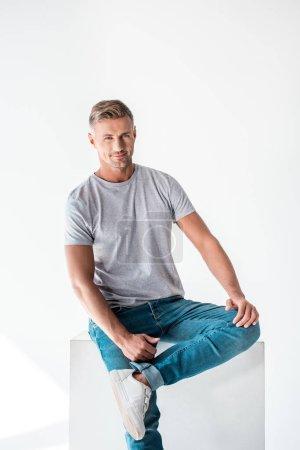 Photo pour Bel homme adulte assis sur un cube blanc et regardant la caméra isolée sur blanc - image libre de droit