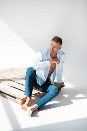 sexy macho sitting on wooden pallet on white and looking away