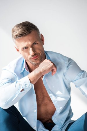 Photo for Handsome sexy man with unbuttoned shirt looking at camera isolated on white - Royalty Free Image
