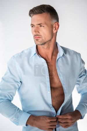 handsome adult man buttoning shirt and looking away isolated on white