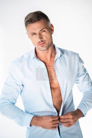 Photo pour Beau macho boutonnage chemise et regarder caméra isolé sur blanc - image libre de droit