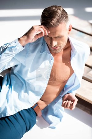 high angle view of handsome macho lying on wooden pallet on white